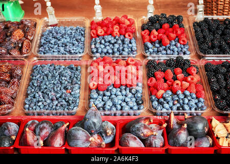 Fresh blueberries, raspberries, blackberries, figs and dry plums displayed in plastic containers on an outdoor market stall - Stock Photo