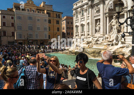 Crowds of tourists near famous Trevi fountain in Rome, Italy. Tourists are making selfie in front of fountain di Trevi, one of the main attractions - Stock Photo