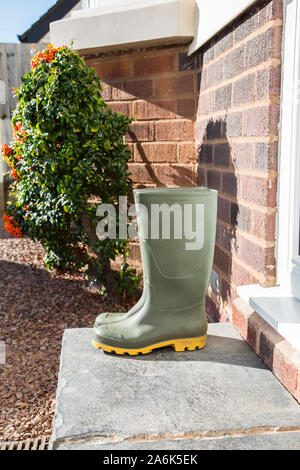 Pair of sunlit, green wellington boots (side view) isolated outdoors on a UK front doorstep after a walk in the autumn sunshine. - Stock Photo