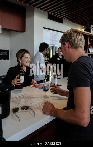A visitor on a wine tasting tour, sampling a glass of red  wine at  the Jacobs Creek visitors centre in the Barossa Valley in south Australia.  There - Stock Photo
