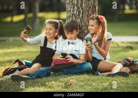 Three school friends are sitting on the grass under a tree and playing their gadgets. Friends do not communicate in life preferring the phone - Stock Photo