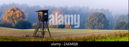 Hunting tower on the edge of the forest during a beautiful sunrise on a foggy morning - Stock Photo