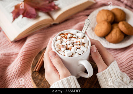 Hot chocolate with marshmallows in female hands. Hot beverage cozy comfort food for autumn and winter holidays season