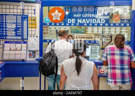 Valencia Spain Estacio del Nord Renfe train railway station inside interior lottery vendor window gambling man woman buying tickets Hispanic Spanish E - Stock Photo