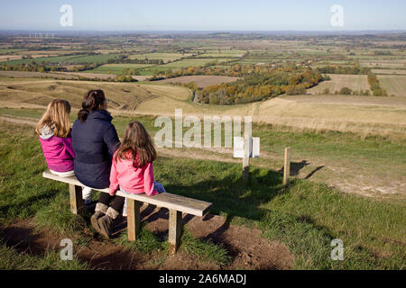Mother and children sat admiring the view from White Horse Hill, Uffington, Oxfordshire. England - Stock Photo