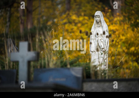 View of Lithuanian cemetery in autumn. White stone sculpture of mourning Mary - tombstone and cross between flowered flowers and yellow trees - Stock Photo