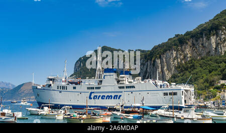 ISLE OF CAPRI, ITALY - AUGUST 2019: Large car ferry operated by Caremar docked amongst small fishing boats in the port on the Isle of Capri. - Stock Photo