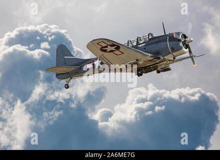 A World War II-era Douglas SBD Dauntless dive bomber flies through dramatic clouds. - Stock Photo
