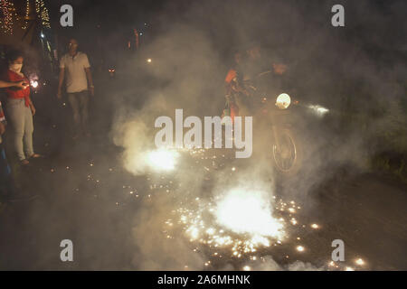 Kolkata, India. 27th Oct, 2019. Few people are seen burning crackers on a roadside while a motorbike passes amidst the smoke during the celebration of Diwali.Diwali is known as the ''festival of lights''. It marks victory of good over evil and light over darkness. Diwali celebration has also created a persistent pollution problem for burning firecrackers in India for years. Credit: Avijit Ghosh/SOPA Images/ZUMA Wire/Alamy Live News - Stock Photo