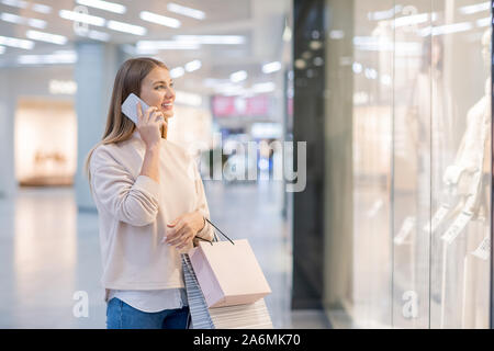 Young woman with paperbags talking to someone on mobile phone by shopwindow - Stock Photo