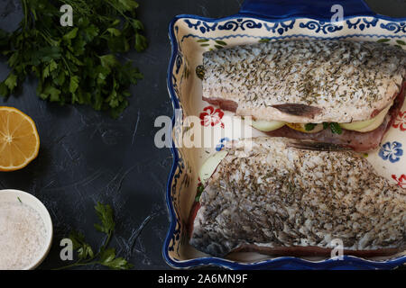 Raw fish stuffed with onions and herbs is located in a ceramic form on a dark background. On the table, salt, lemon, dill and parsley - Stock Photo