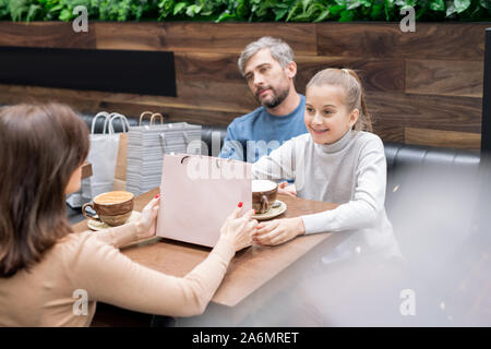 Pretty girl and her mother with paperbag looking at one another by table in cafe - Stock Photo