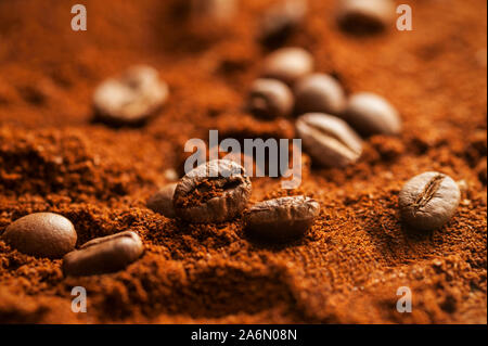 Roasted coffee beans and ground coffee. Macro shooting with selective focus.. Background in horizontal orientation.