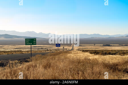 Straight Highway through the Nevada desert leading to a vanishing point in the distance. - Stock Photo