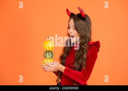 Surprise trick. Surprised child hold pumpkin stack orange background. Little girl wear red devil horns with surprise emotion on face. Small kid keep mouth opened of big surprise. Halloween surprise. - Stock Photo