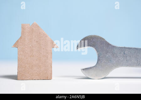 Abstract cardboard house next to a wrench. Real estate repair concept. Close up. - Stock Photo