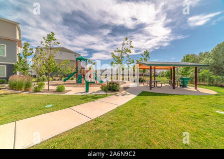 Park at a sunny neighborhood with childrens playground and pavilion eating area - Stock Photo