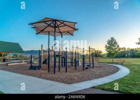 Slides and climbing structures at a childrens playground against sky at sunset - Stock Photo