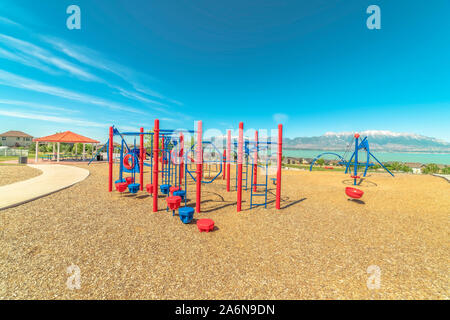 Park with vivid childrens playground and pavilion picnic area overlooking lake - Stock Photo