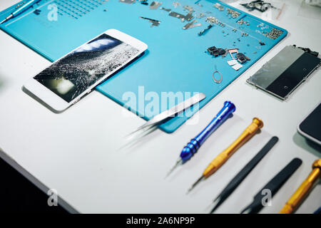 Smartphone with smashed screen, tools and details on desk of repairman