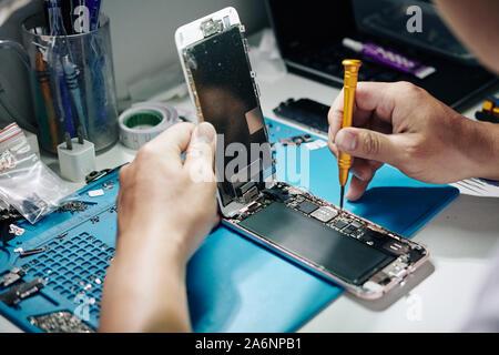 Repairman removing smartphone screen and screws securing SIM card tray - Stock Photo
