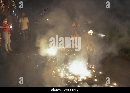 Kolkata, India. 27th Oct, 2019. Few people are seen burning crackers on a roadside while a motorbike passes amidst the smoke during the celebration of Diwali.Diwali is known as the 'festival of lights'. It marks victory of good over evil and light over darkness. Diwali celebration has also created a persistent pollution problem for burning firecrackers in India for years. Credit: SOPA Images Limited/Alamy Live News - Stock Photo