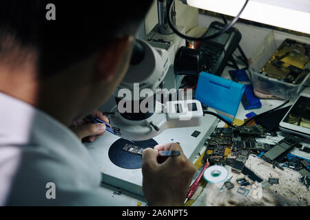 Repairman sitting at desk with broken smartphone parts and looking at logic board through microscope - Stock Photo