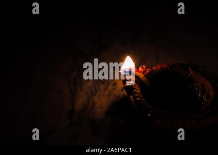 earthen oil lamp lit on the occasion of deepavali, a hindu festival of light with selective focus on lamp and background and foreground blur - Stock Photo