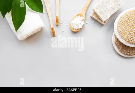 Zero waste bathroom accessories, natural brush,  sea salt,  tooth brush, towel and soap on white background. Flat lay. - Stock Photo