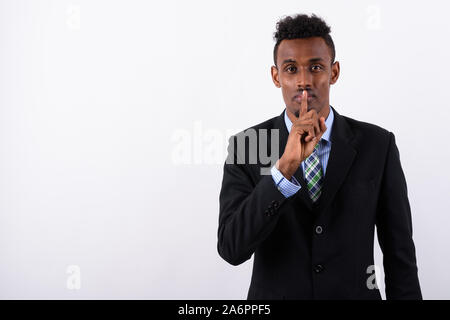Young bearded African businessman wearing suit against white bac - Stock Photo