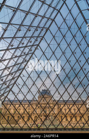 Nice portrait view of the Richelieu Wing through the square glass panes of the Louvre Pyramid in Paris from the underground lobby. - Stock Photo