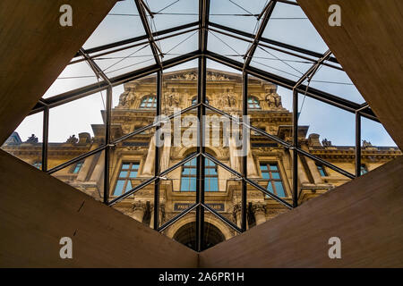 Artistic view of the beautiful façade of the Richelieu Wing through a diamond shaped opening, covered with the glass panes of the Louvre Pyramid in... - Stock Photo