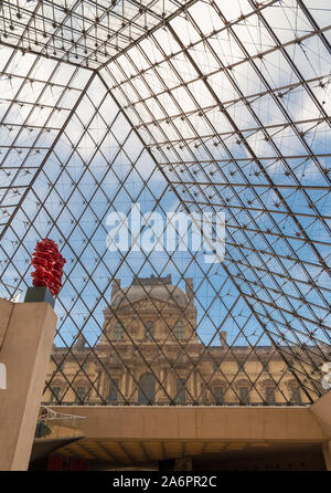 Great portrait view of the Richelieu Wing through the glass of the Louvre Pyramid in Paris from the underground lobby with the red sculpture Versus of... - Stock Photo