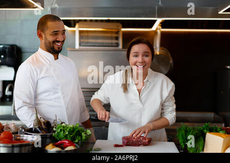 Handsome young African chef is cooking together with Caucasian girlfriend in the kitchen A cook teaches a girl how to cook. Man and woman cooking in p - Stock Photo