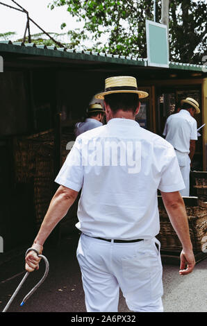 Monte, Madeira, Portugal - Sep 14, 2019: Wicker Basket Sledges driver, Carreiros do Monte. Traditional mean of transport between Monte and Funchal, now attraction for tourists. Typical straw hat. - Stock Photo