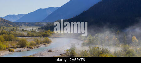 Foggy trees at the river in the Isar Valley, at Vorderriss with parts of the Pfetter Kopf, the hazy Grasberg and Bruensteck Mountains, Upper Bavaria - Stock Photo