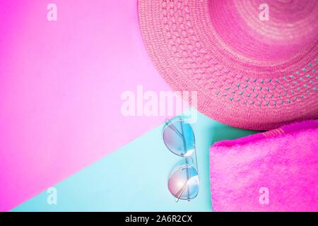 Flat lay of straw sun hat, sunglasses, pink towel on on two tone blue and purple background. Top view with copy space, frame. Summer, vacation, beach, - Stock Photo