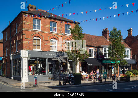 Marlow High Street in Buckinghamshire with shops, cafes and bunting across the street with a clear blue sky - Stock Photo