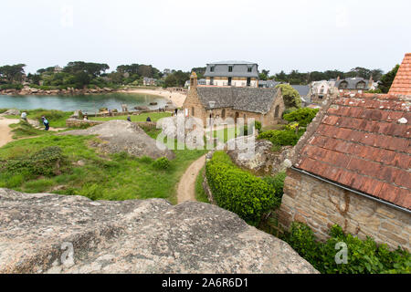 Village of Plouhmanac'h, France. Picturesque view of Ploumanac'h's Plage Saint-Guirec with the Chapel of Saint-Guirec in the centre of the image. - Stock Photo