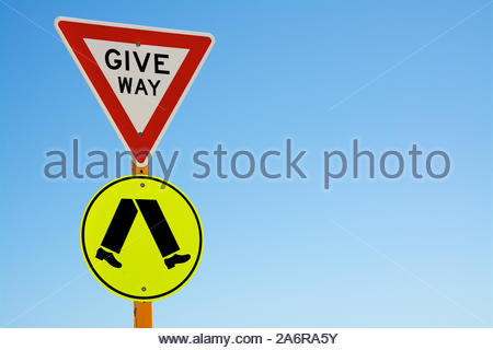 A give way to pedestrians sign with a blue sky background and copy space on the right. - Stock Photo