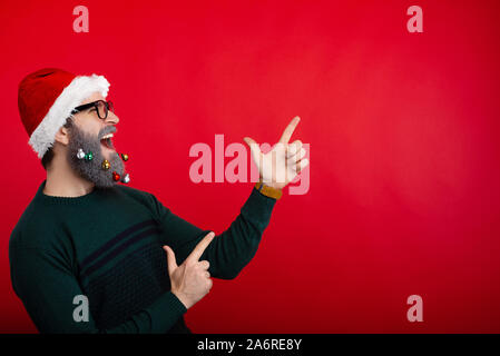 Photo of crazt man screaming and pointing at copyspace over red background and wearing santa claus hat