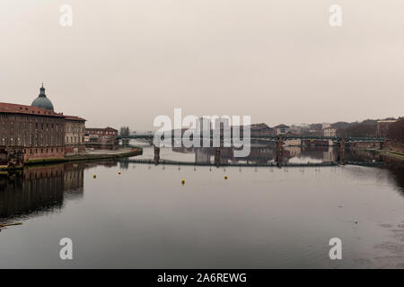 a view of the Garonne River as it passes through Toulouse, France, in a foggy day with the bridge Pont Saint Pierre in the background and the Hotel-Di - Stock Photo