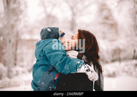 Happy mother holding son while standing in park during winter
