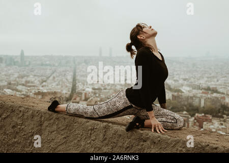 Young woman practicing yoga, stretching. Barcelona - Stock Photo
