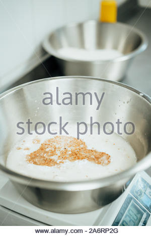 Male baker prepares dough for baking grain bread with flax seeds - Stock Photo