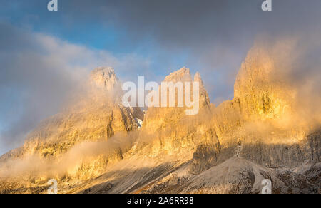 Foggy mountain landscape during sunrise  of the picturesque Dolomiti at Passo Sella area in South Tyrol in Italy. - Stock Photo