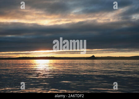 Early morning silhouette, against a cloudy sunrise, of St. Michael's Mount across Mounts Bay from near Newlyn, Cornwall, England, UK - Stock Photo