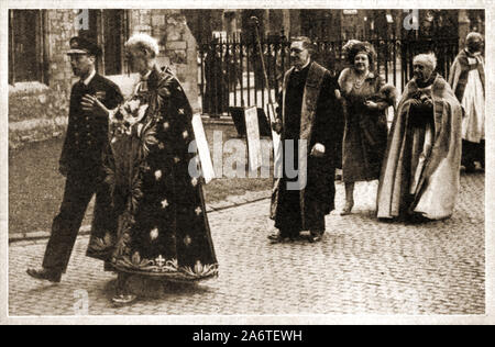 MAUNDAY  / MAUNDY MONEY  Circa 1940's - King George VI of England joins high ranking clergy and Queen Elizabeth his wife (walking behind) for the  the annual ceremony of distributing Maundy Money after the a religious service in the Church of England held on Maundy Thursday, the day before Good Friday when the British monarch ceremonially distributes small silver coins known as 'Maundy money' as symbolic alms