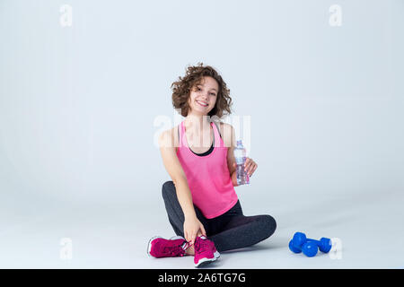Young fitness woman drinks water and relaxes after training with dumbbells, on a gray background. - Stock Photo
