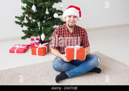Christmas and holidays concept - Funny man in santa hat holding a gift at home in the living room - Stock Photo